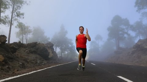 Running sport fitness runner man. Male athlete running and sprinting on mountain road into fog in full body in amazing nature landscape. Fitness model training outdoors for marathon run.