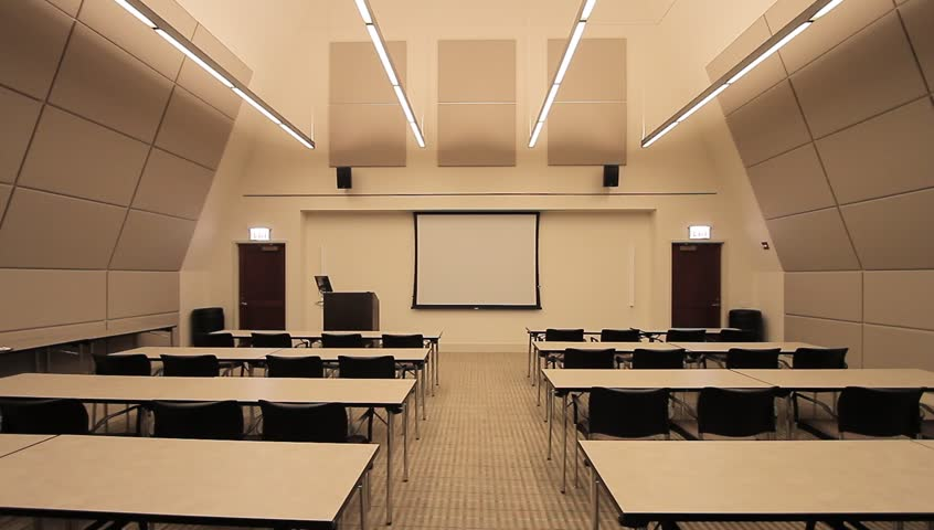 lecture classroom business. The inside of a lecture room/classroom at an industrial firm. There is a projector in the center on the wall, and tables that sit accordingly to listen to the speaker.