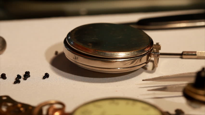 A close up of a man opening the back of an old pocket watch and examining the inside mechanisms.