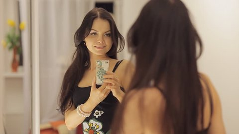 Young pretty girl dances and takes a photo of herself before the mirror Full HD 1080 NTSC