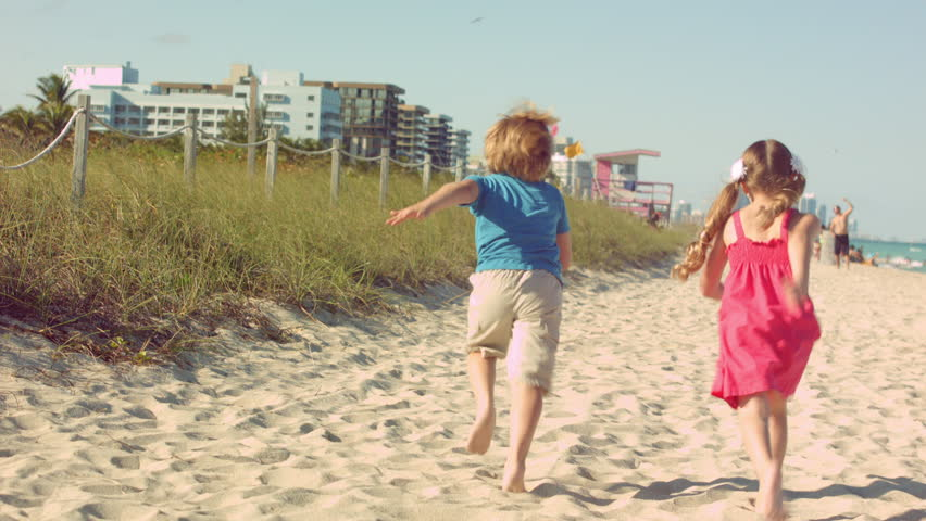 Two Little Kids Running Down The Beach Away From Camera Stock Footage Video 5976191