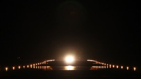 Airliner taking off from an airport in the night, head-on