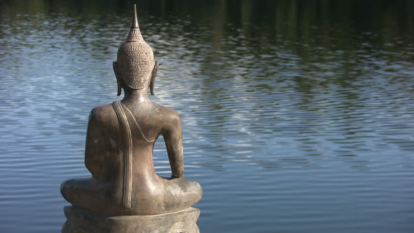 Buddha by the lake.  A seated statue of Buddha sits by the lake. Space for text on right side.