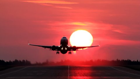 Airliner passing in front of the sun while taking off during the sunrise, head on