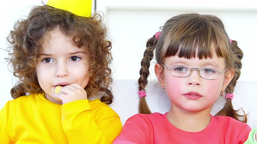 Little girls eating potato chips on the birthday party.Slow motion, high speed camera
