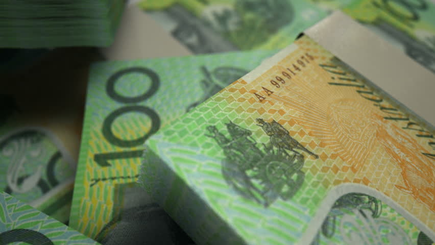 An extreme closeup pan across variously placed bundled wads of Australian dollar banknotes