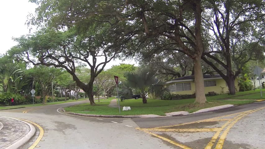 CORAL GABLES, FLORIDA - JAN 2014: Coral Gables tree lined street POV. Point of view driving. One of the first master planned communities to maintain a standard level of luxury and property values.