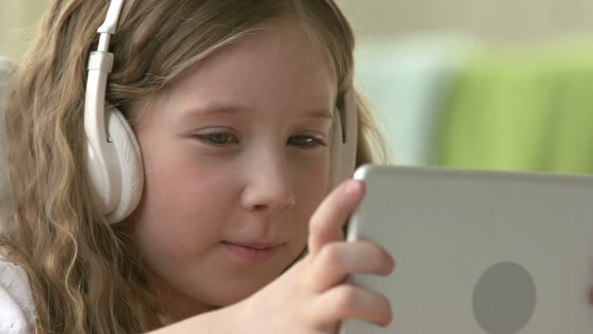 Little girl in earphones using hi-tech tablet and mumbling something to herself