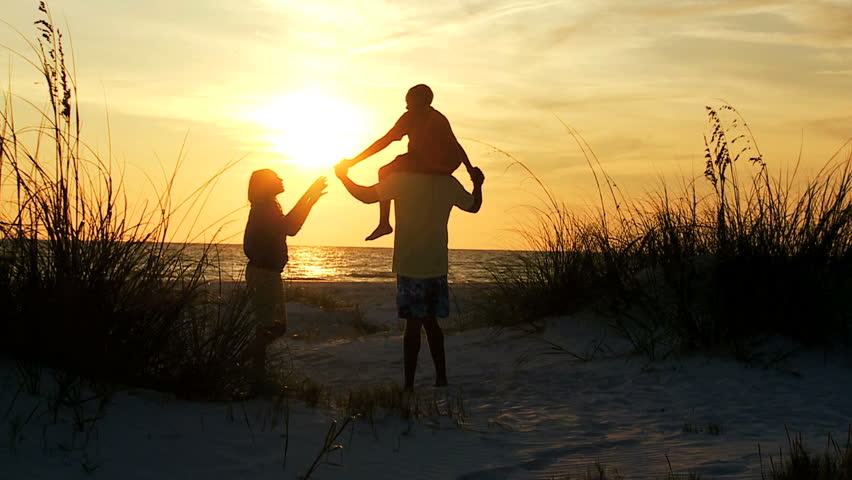 young boy on fathers shoulders as family in silhouette stand on beach watching sunset slow motion son riding fathers shoulders silhouette beach stock