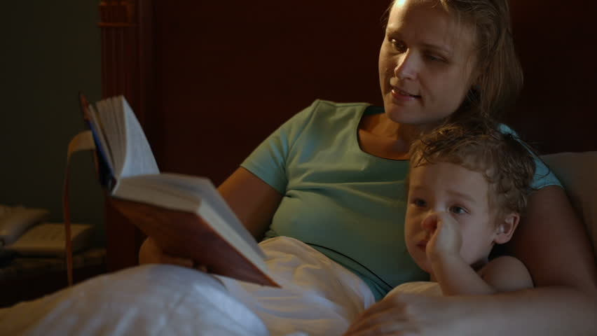 Tilt shot of mother and son in bed at night. Mom reading aloud before bed,  boy watching TV