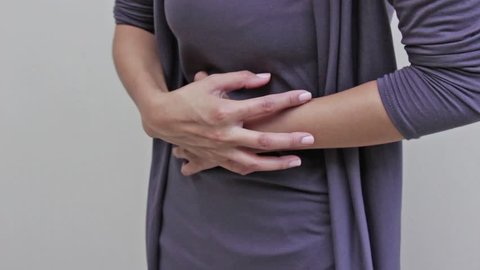 menstruation pain or stomach trouble, woman hand holding her belly, body closeup quarter view