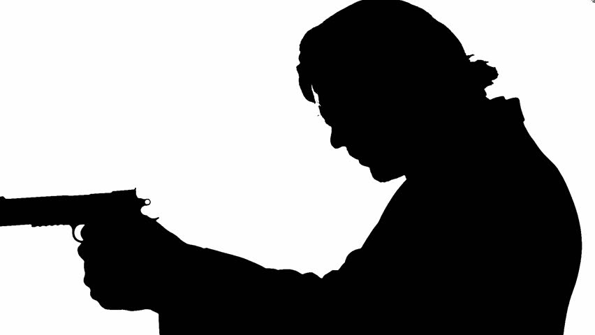 Silhouette of a man with a gun walking and aiming down the sights of his pistol. He could be a hit man or just security police looking for enemy combatants.