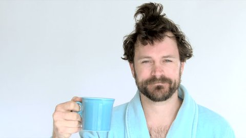 Model released man in studio wearing blue robe drinking coffee in the morning.