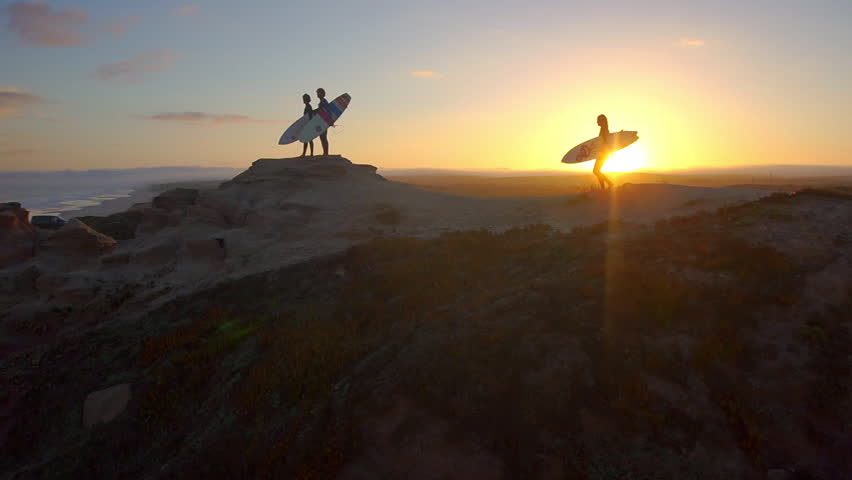 AERIAL: Surfers watching waves at sunset
