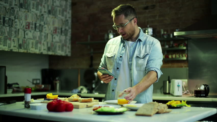 man using a cellphone and eating pepper in the kitchen