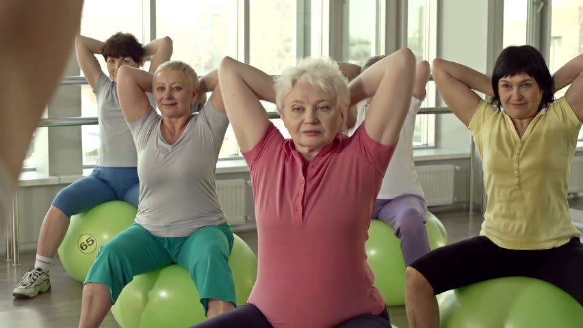 Dolly of unrecognizable coach instructing women to exercise with the ball