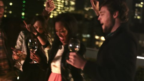 A group of friends hang out on a rooftop bar at night and dance around the fireplace