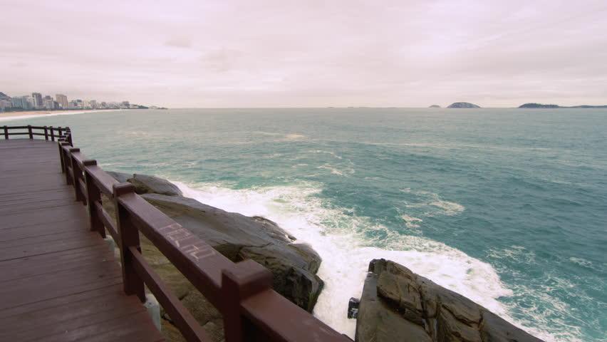 Slow motion tracking shot of splashing waves on rocks under a bridge in Rio de