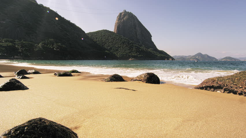 Tracking slow motion shot of Red Beach in Rio with waves washing over exposed boulders.