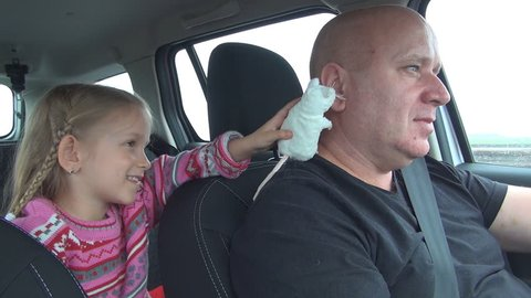 Little Girl Playing with Mouse Toy Bothering her father while Driving, Man Driving, Family in Car, Driver in a Trip