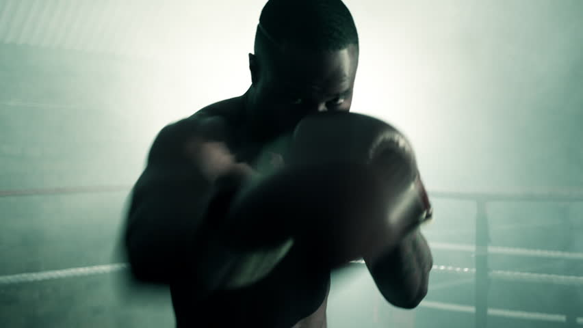 Male Boxer punches firecly inside the Boxing Ring