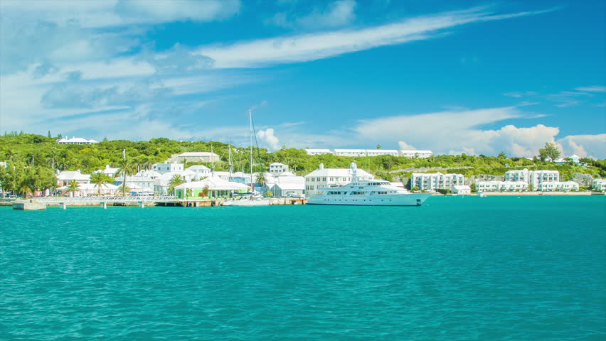 Departing St. George's Harbor in Bermuda on a Ferry in Tropical Turquoise Waters on a Sunny Day. Featuring a Luxury Yacht with Hotel Buildings.