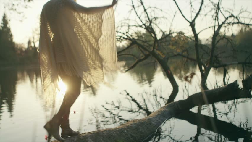 A girl walks across a fallen tree that is resting in a pond   Shutterstock HD Video #6119681