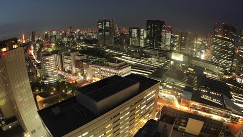 Day to night aerial view time lapse of the Shinagawa area located in Tokyo, Japan.  This time lapse shows the city lights and skyscrapers illuminating as the sky turns from daytime to nighttime.