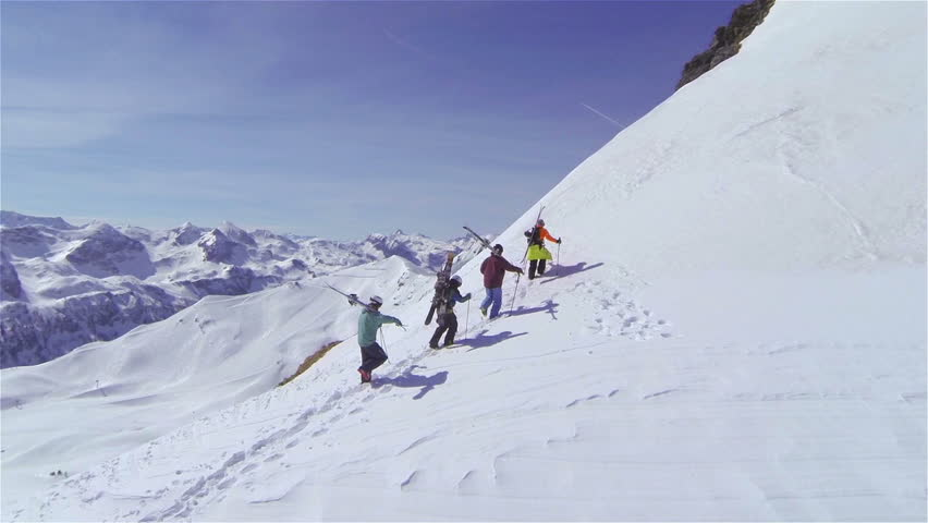 AERIAL: Skiers hiking uphill, carrying the skis