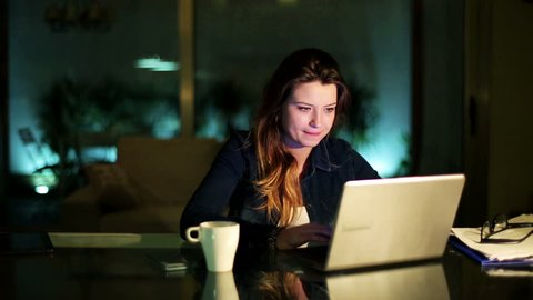 Woman working on laptop at night at home and drinking coffee.