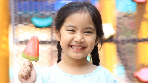 Happy little Asian girl enjoy eating with icecream on playground