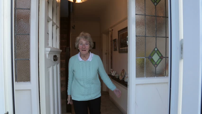 Senior woman opens front door and welcomes visitor, steadicam shot