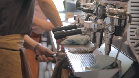 Professional barista prepares a latte in a busy coffee shop