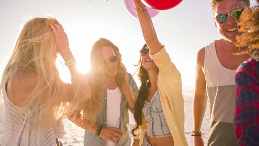 Friends dancing with balloons on beach