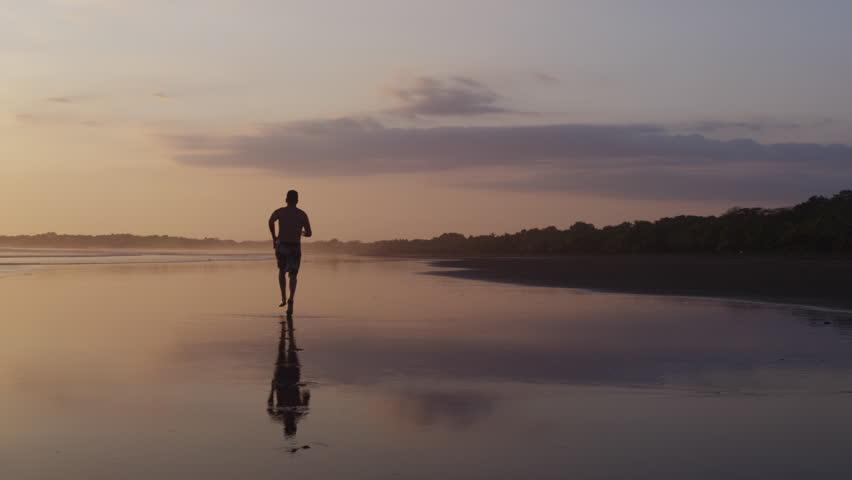 Costa Rica, Esterillos Beach, Man running on beach at sunset