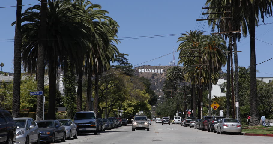 LOS ANGELES, USA - APRIL 3, 2013 Hollywood Sign Los Angeles Entertainment World Symbol Cars Passing Palm Trees ( Ultra High Definition, Ultra HD, UHD, 4K, 2160P, 4096x2160 )
