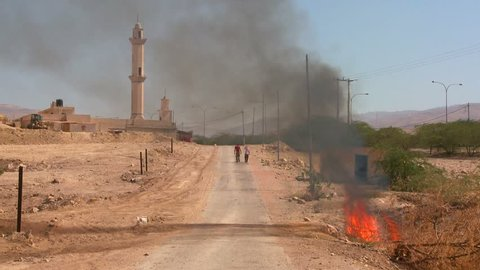 PALESTINIAN TERRITORIES, ISRAEL CIRCA 2013 - A fire burns on a lonely road near a mosque in the Palestinian Territories.