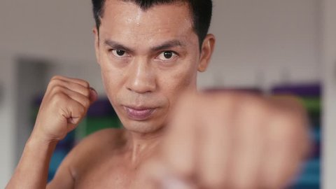 Athlete training, workout, exercise in combat sport gym and fitness club, boxing and martial arts for wellness and wellbeing. Portrait of strong asian man punching, fighter staring at camera. 16of29