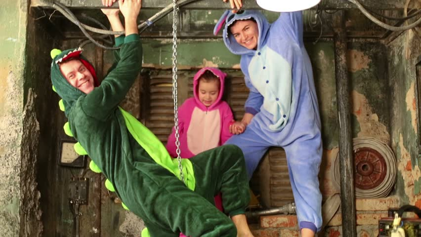 Family in colorful costumes of dragons play at very old room with table and samovar