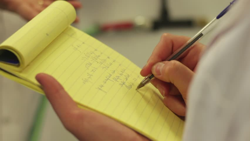 Close up on a person taking notes on a yellow paper tablet