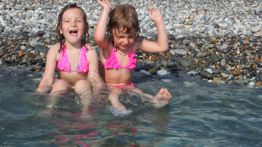 Two Little Girls Lying On Pebble Beach With Sea Surf Stock -6051