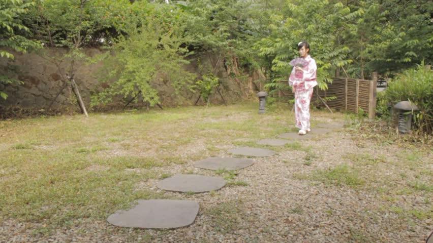 Asian woman in kimono walking down a path in a Japanese garden | Shutterstock HD Video #6308741