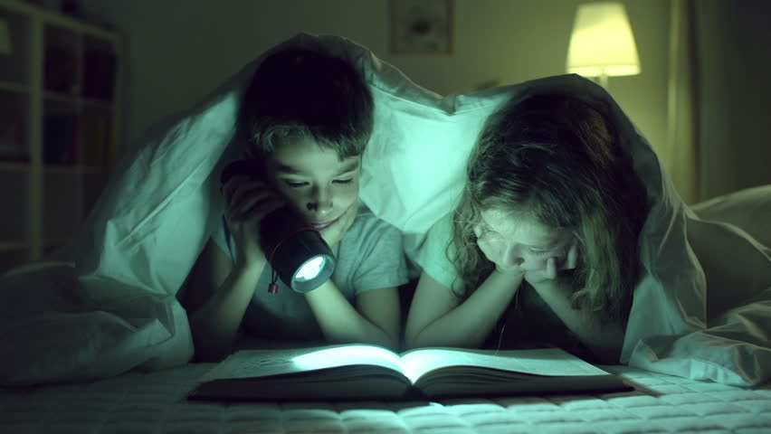 Children reading one book, girl blocking vision to boy with her finger