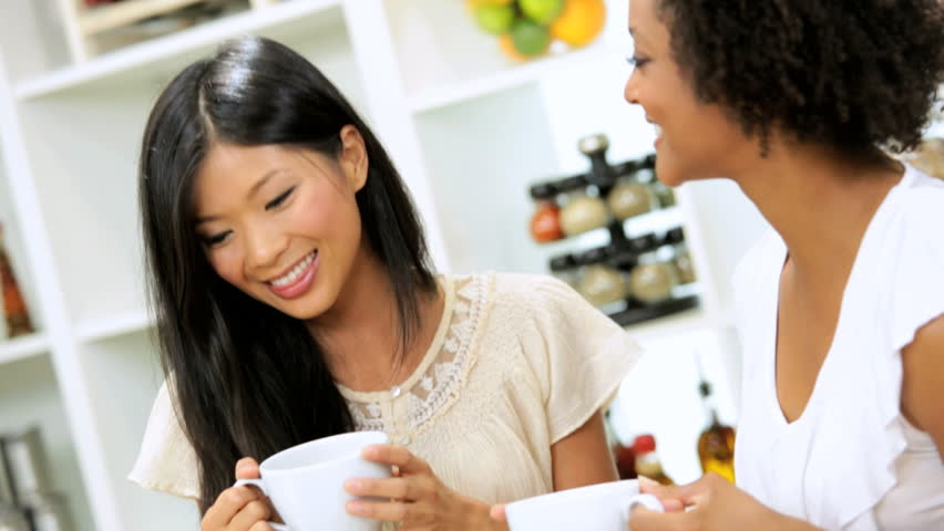 Young Multi Ethnic Female Students Working Laptop Home - Young multi ethnic female students drinking coffee while working with wireless laptop home kitchen searching information | Shutterstock HD Video #6329951
