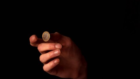 Woman tossing a euro coin on black background in slow motion
