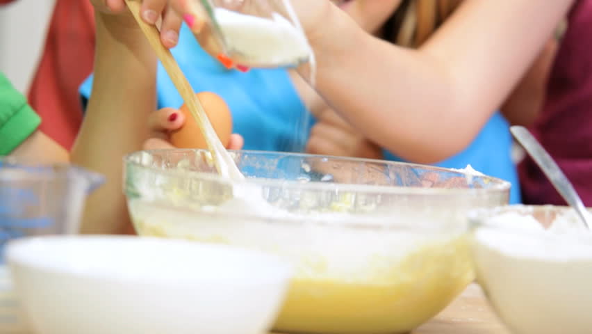 Hands Blonde Caucasian Family Home Kitchen Baking Together - Hands no faces young blonde Caucasian sisters brother home kitchen counter adding sugar eggs homemade cake baking mixing bowl