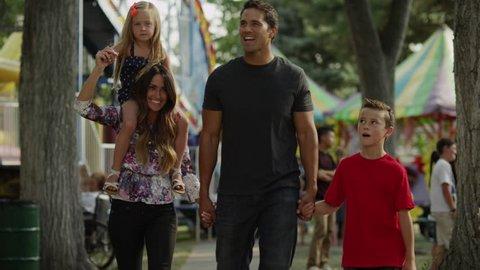 Medium shot to close up of family walking at carnival