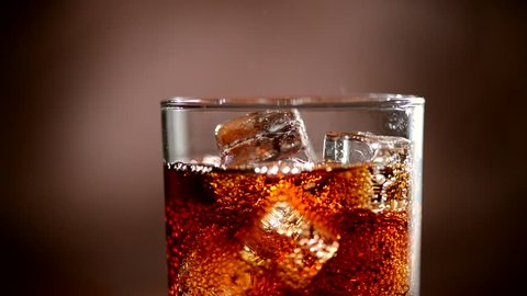 Cola with Ice and bubbles in glass. Cola pouring. Stock full HD video footage 1920x1080p