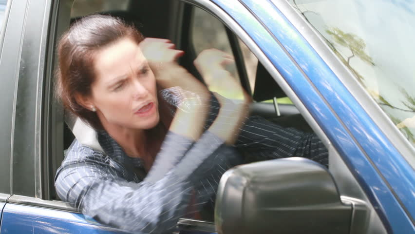 A frustrated furious woman is angry and screams in her car.