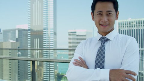 Successful young Asian Chinese businessman rooftop modern office skyscraper building smiling camera head shoulders portrait shot on RED EPIC